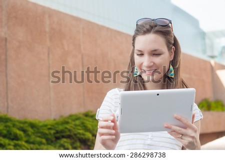 Young woman using digital tablet pc outdoors in a city