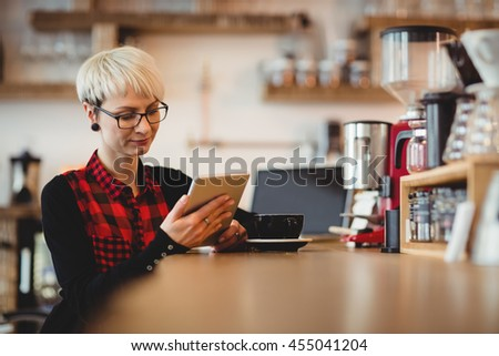 Young woman using digital tablet while having coffee at office cafeteria - stock photo