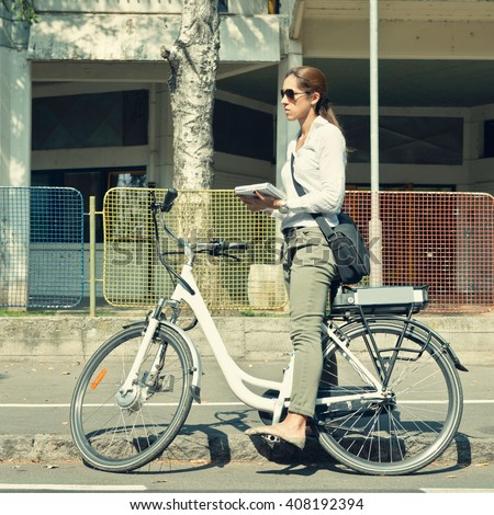 Young woman using electric bicycle to get to work in a city - stock photo