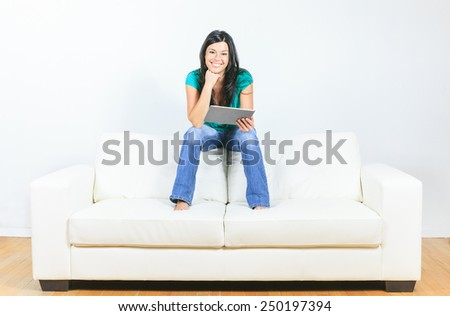 Young woman using electronic tablet sitting on sofa - stock photo