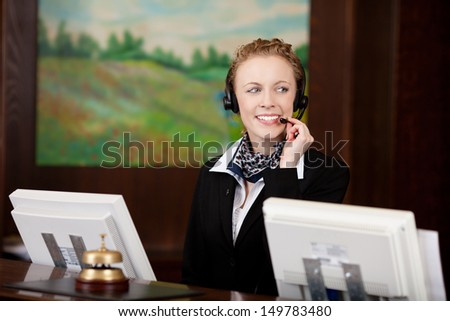 Young woman using headset while working at the reception of a hotel - stock photo