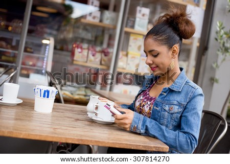 young woman using her phone at a coffee shop