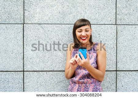 Young woman using her phone in the city smiling. - stock photo