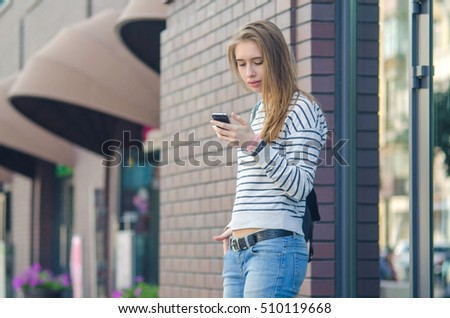 Young woman using her phone on the street