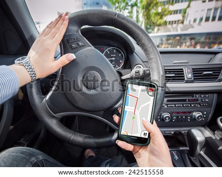 Young woman using her smartphone as GPS navi to make her way trough the city. - stock photo