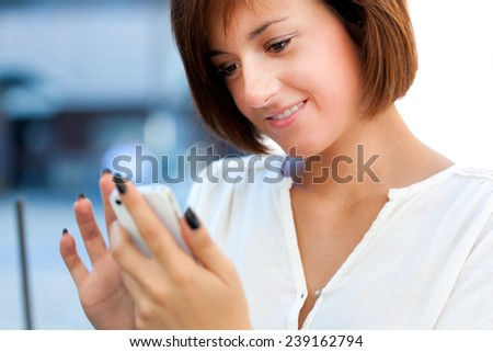 Young woman using her smartphone outdoor  - stock photo