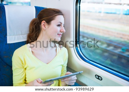 Young woman using her tablet computer while traveling by train (color toned image; shallow DOF) - stock photo