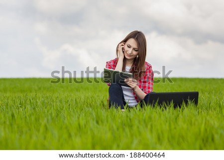 young woman using laptop and cell phone