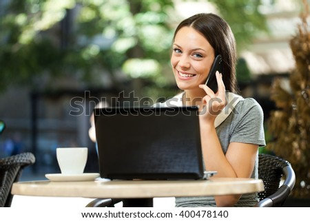 Young woman using laptop and talking on phone in a cafe