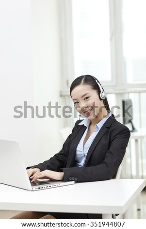 Young woman using laptop and wearing headset