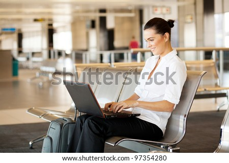 young woman using laptop computer at airport - stock photo