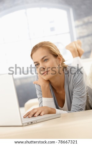 Young woman using laptop computer at at home, looking at screen.? - stock photo