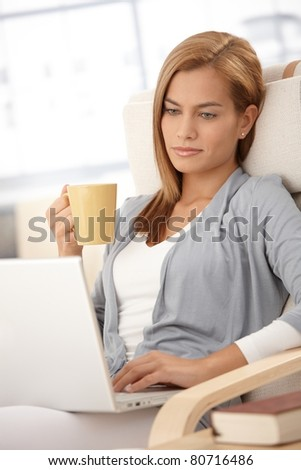 Young woman using laptop computer at home, holding tea cup, looking at screen, thinking.? - stock photo