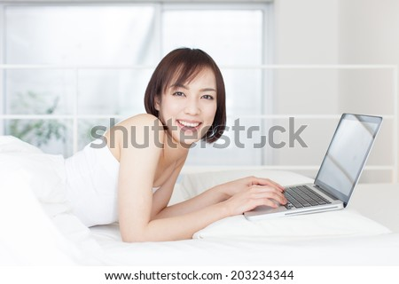 young woman using laptop computer on the bed