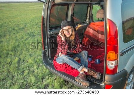 Young woman using laptop computer sitting in car relaxing and enjoying her trip - stock photo