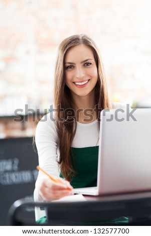 Young woman using laptop in cafe