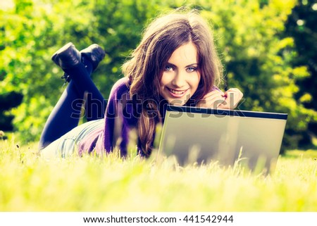 Young woman using laptop in the park lying on the green grass. Leisure time activity concept. Instagram filter - stock photo