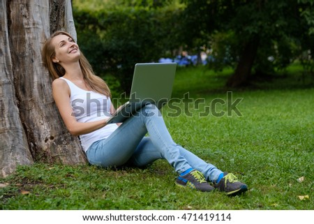 Young woman using laptop in the park sitting on the grass