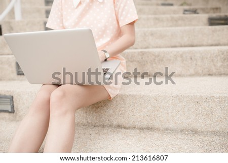 Young woman using laptop on steps outdoors
