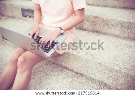 Young woman using laptop on steps outdoors - stock photo
