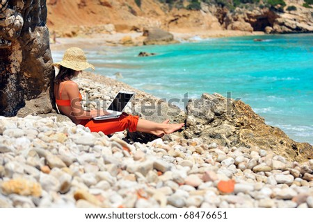 young woman using laptop on the beach