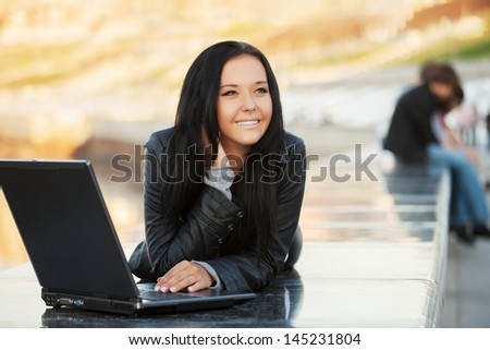 Young woman using laptop on the sidewalk - stock photo