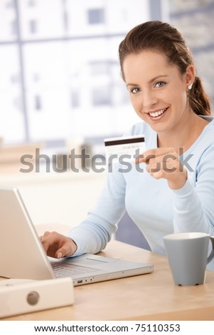 Young woman using laptop, shopping on internet, using credit card, smiling.? - stock photo