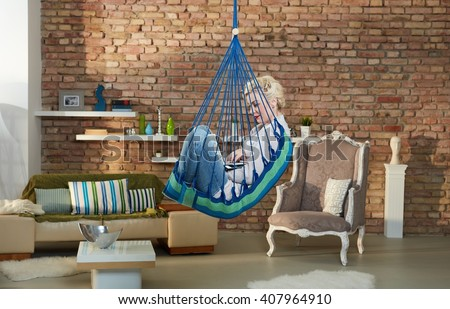 Young woman using laptop, sitting in hammock like chair in retro home.