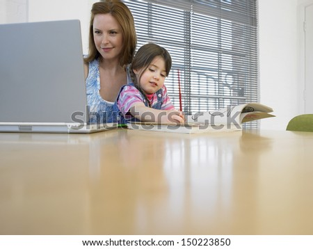 Young woman using laptop while daughter coloring book at table in house - stock photo
