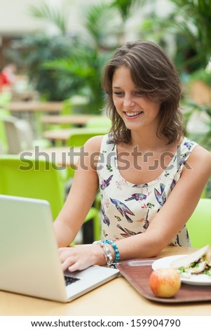 Young woman using laptop while having meal in the cafeteria - stock photo
