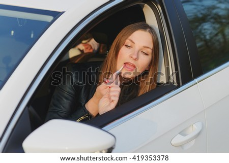 young woman using lipgloss in white car - stock photo