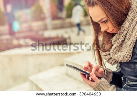 Young woman using mobile on the street. Young woman using mobile telephone on the street - stock photo