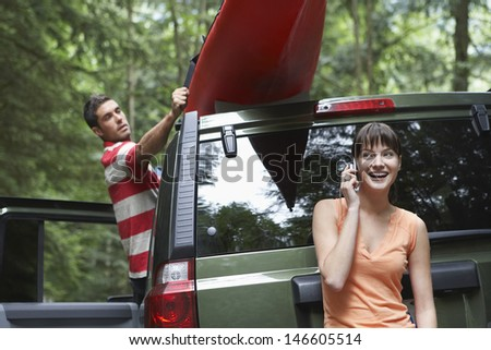 Young woman using mobile phone as man tie kayak on car roof in the forest - stock photo