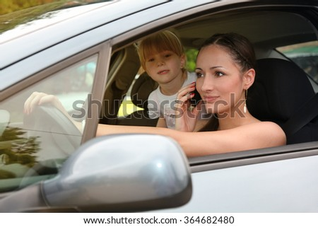 Young woman using mobile phone during driving a car, her daughter standing back, don't using safety seat ,Unsafe drive on the road! - stock photo