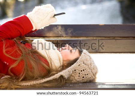 Young woman using mobile phone outdoors - stock photo