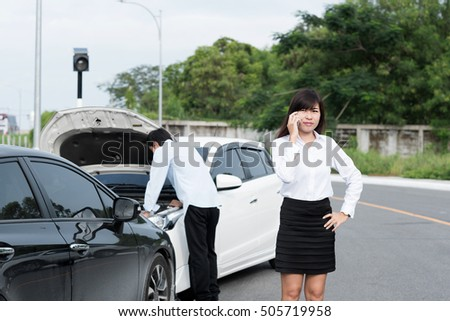 young woman using mobile phone while car accident