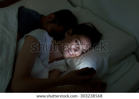 Young woman using mobile phone, while husband asleep - stock photo