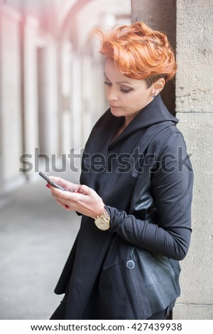 Young woman using mobile telephone on the street - stock photo