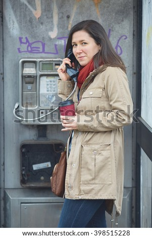 Young woman using old phone booth - stock photo