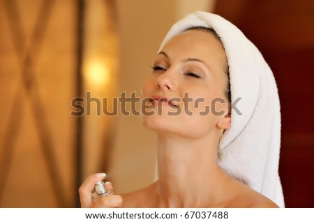 young woman using perfume - stock photo