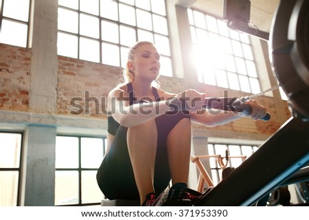 Young woman using rowing machine in the gym. Caucasian female doing cardio workout in fitness club. - stock photo