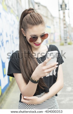 Young woman using smart phone in the street with graffiti.
