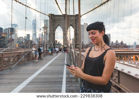 Young Woman Using Smart Phone on Brooklyn Bridge - stock photo