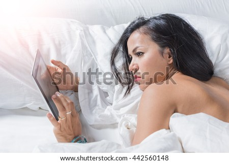 young woman using smart phone on the bed. (intential sun glare)