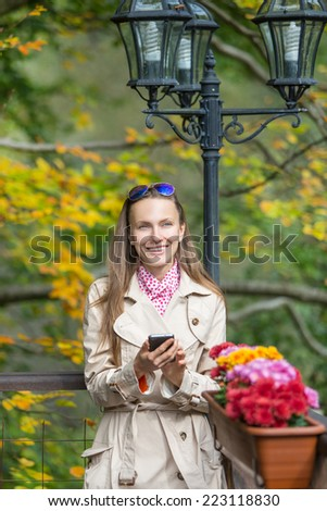 Young woman using smart phone - while standing on beautiful autumn background. copy space - stock photo