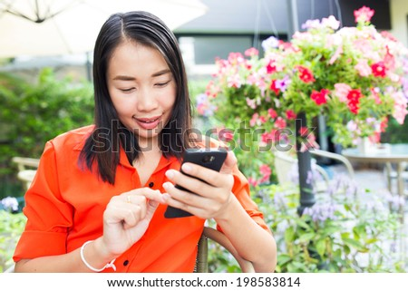 Young woman using smartphone in a sidewalk cafe restaurant with beautiful garden - stock photo