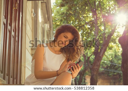 Young woman using smartphone outdoors.