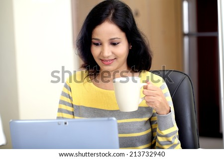 Young woman using tablet computer and drinking coffee