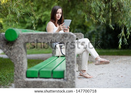 Young woman using tablet computer in a park. Sitting on a bench. - stock photo