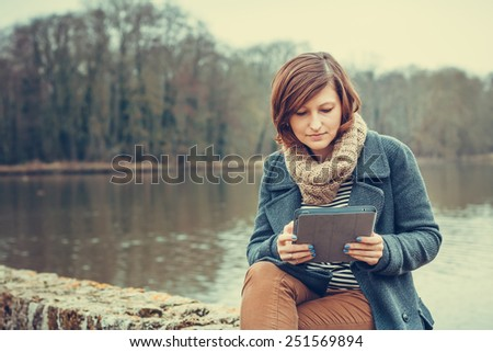 Young woman using tablet computer outdoors - stock photo